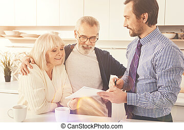 Positive aged couple talkign with real estate agent