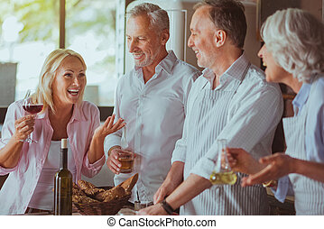 Positive aged friends getting ready for festive dinner