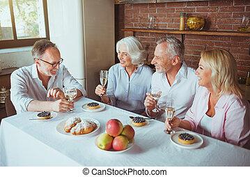 Positive aged frineds having celebration at home