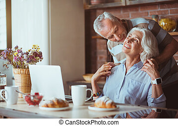 Positive aged lovign couple resting in the kitchen