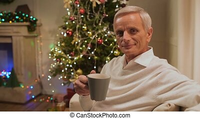 Positive aged man drinking tea at home