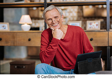Positive aged man holding a tablet