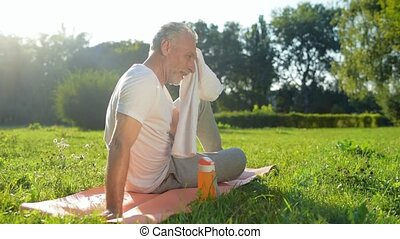 Positive aged man resting after sport exercises