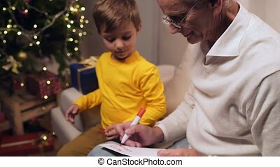Positive aged man signing Christmas card with his little grandson
