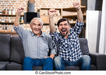 Positive aged man sitting with his son