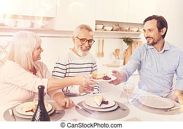 Positive aged parents enjoyign meal with their adult son
