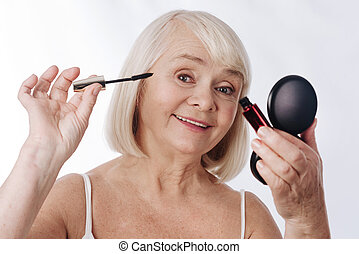 Positive aged woman using mascara