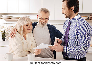 Positive aging couple owners meeting financial adviser at...
