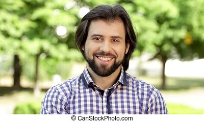 Positive and bearded man is looking on camera and smiling a...