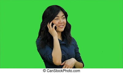 Positive and happy asian woman talking on a cell phone on a Green Screen, Chroma Key