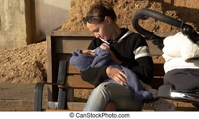 Positive and smiling mama feeding baby outdoor on a bench having rest
