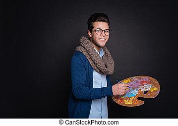 Positive artist holding color palette