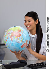 Positive asian businesswoman holding a globe