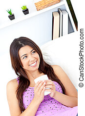 Positive asian woman holding a cup of coffee at home