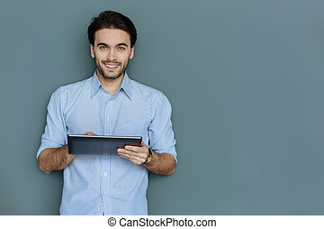 Positive attractive man holding a tablet