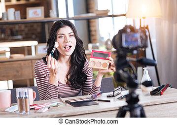 Positive attractive woman doing makeup