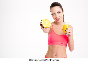 Positive attractive young sportswoman showing an orange half...