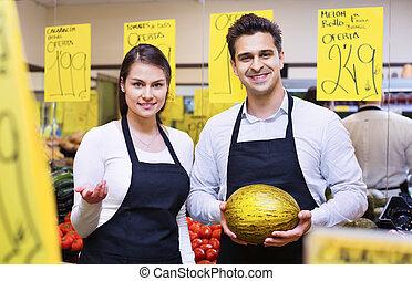 Positive beautiful seller holding musk-melon in market, ...