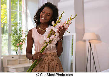 Positive beautiful woman holding flowers at home