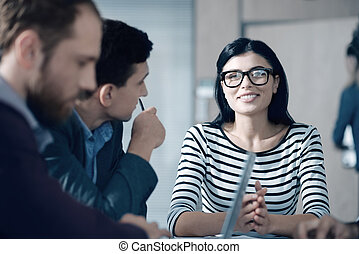 Positive beautiful woman sitting at the table with her colleagues