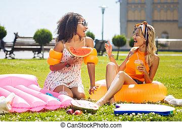Positive beautiful women having interesting conversation and smiling