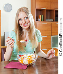 blonde girl eating fruit salad in home