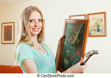 Positive blonde girl hanging pictures in frames