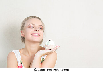 Positive blonde girl having fun with a sweet dessert with butter cream. Space for text