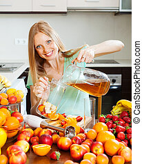 girl making fresh beverages with fruits at home kitchen