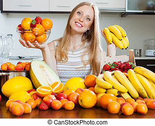 woman with bananas and other fruits in home kitchen