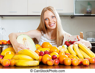 blonde long-haired woman with heap of fruits