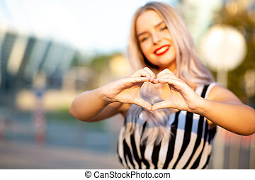 Positive blonde model with red lips making heart sign with her fingers at the street. Space for text