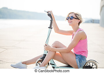 Positive blonde woman sitting at blue kick scooter