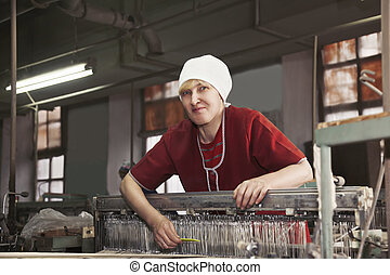 Positive blonde woman with comb at the factory