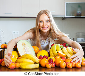blonde woman with heap of fruits