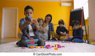 Positive boy creating construction with toy bricks