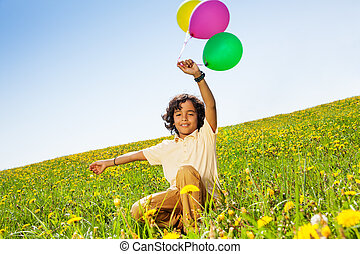 Positive boy with flying balloons in summer