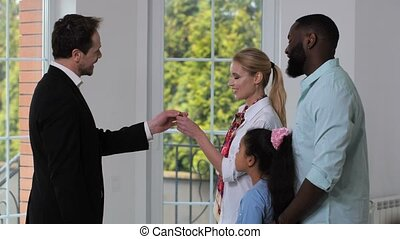 Positive broker handing keys to happy homeowners - Side view...