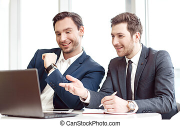 Positive business partners sitting at the table