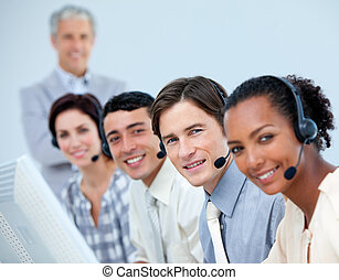 Positive business people using headset in a call center