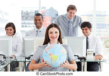 Positive business team holding a globe in the office