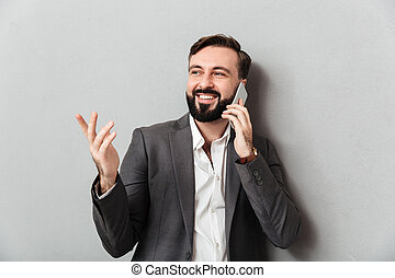 Positive businesslike guy in formal wear mobile chatting gesturing while using cell phone, isolated over gray background
