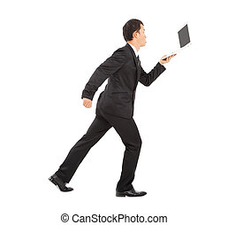 positive businessman running busily and holding a laptop