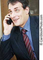 Positive businessman talking via phone