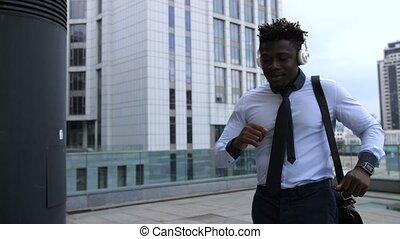 Positive businessman with headphones dancing outdoors