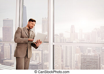 Positive businessman working on the laptop