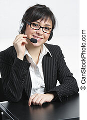 Positive businesswoman with headset sitting at desk
