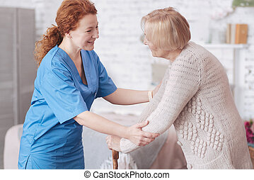 Positive caregiver having pleasant conversation with retired lady