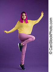 positive charming girl standing on one leg and posing to the camera