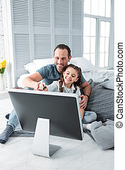 Positive cheerful girl spending time with her father